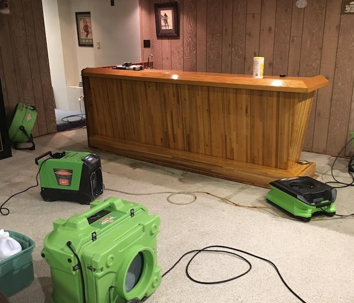 Airmovers drying a basement bar area with wood paneling