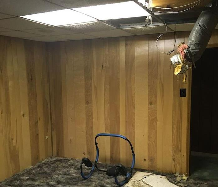 Basement with damaged ceiling and wood paneling
