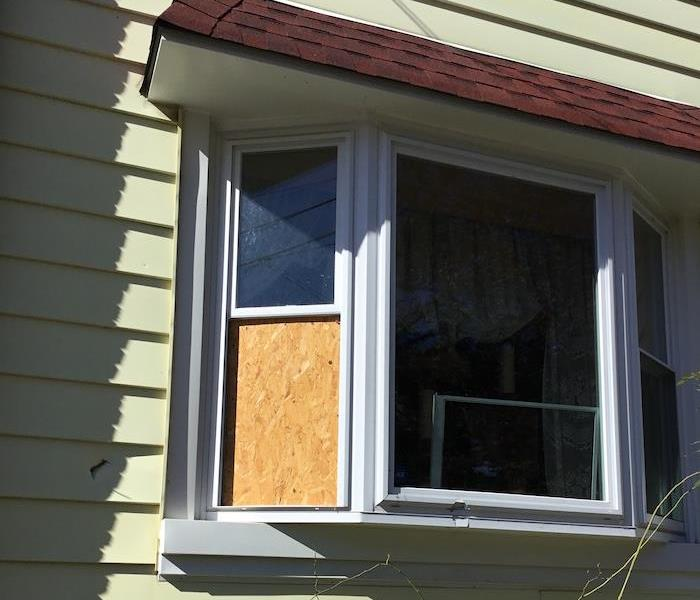 Window on home boarded up by SERVPRO