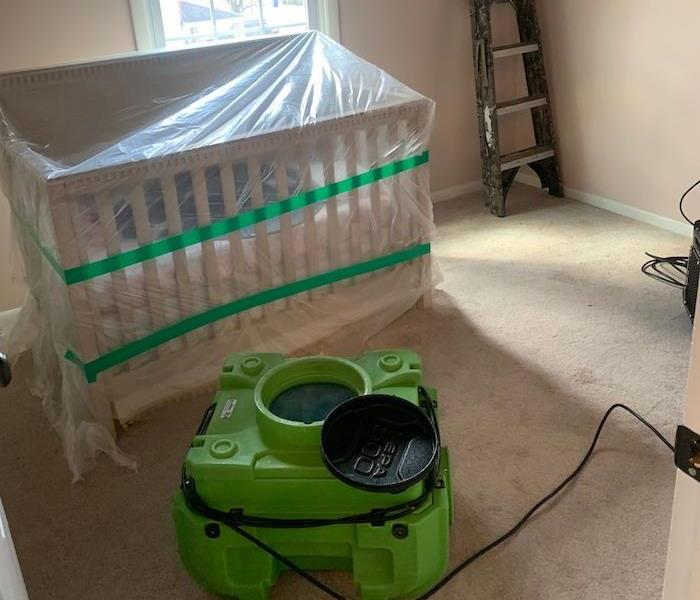 Room with plastic-covered crib and SERVPRO drying equipment
