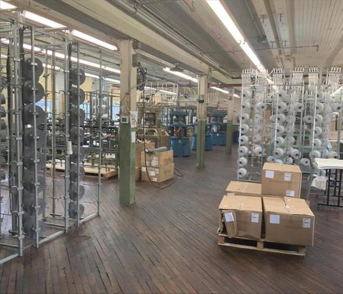 large interior warehouse, wooden floor, and spools of materials, fogged and cleaned