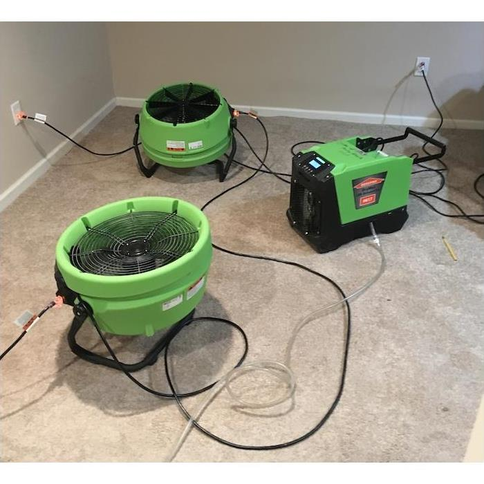 Green equipment sitting on tan carpet in a room