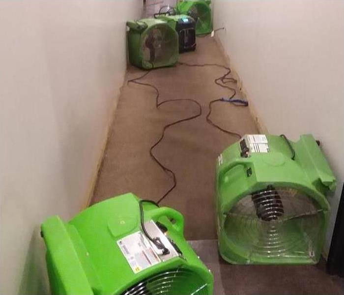Three pieces of equipment set in a hallway drying the floor after water damage hit