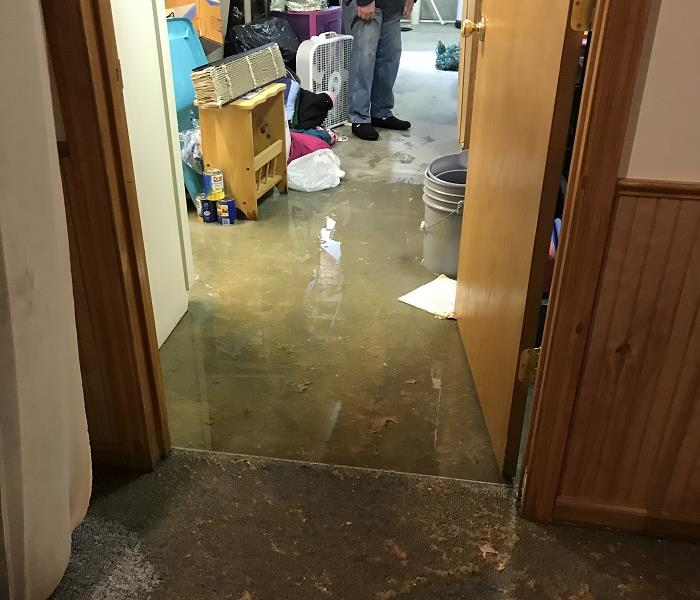 Flooded basement.  Water on floor, wet belongings