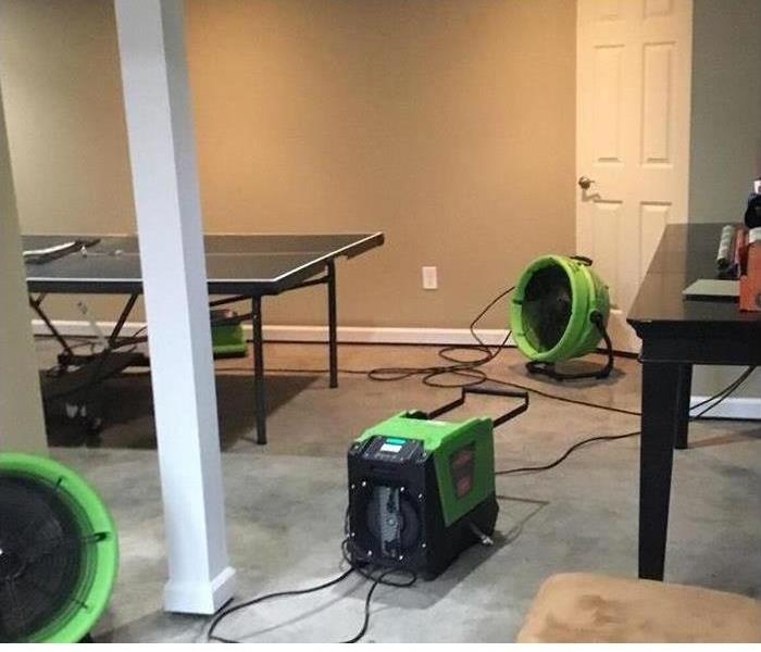 Water removal equipment set out on a carpet damaged by water in a game room