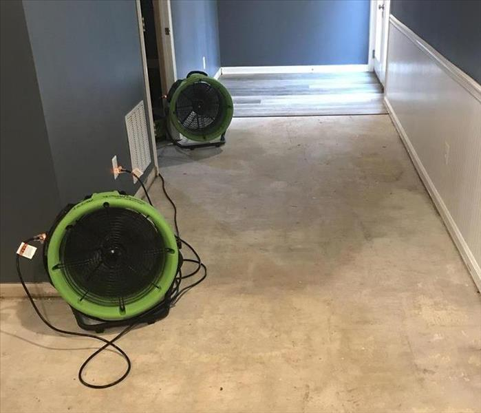 SERVPRO equipment on the floor of a room with grey walls.