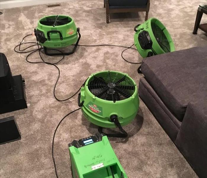 A carpeted room with SERVPRO equipment on the floor.
